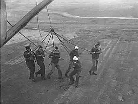 ground handlers holding down stern of blimp during masting operation.
